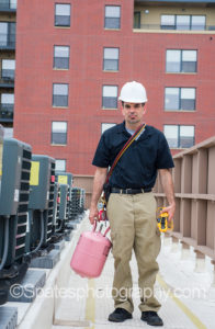 Hvac Training - Technician with air conditioning repair tools on rooftop