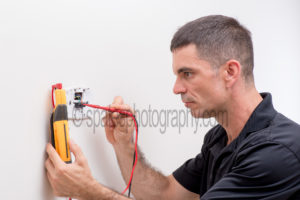 AC repairman checking voltage on a digital thermostat