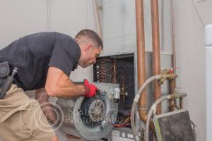 hvac technician installing blower motor in a commercial heat pump