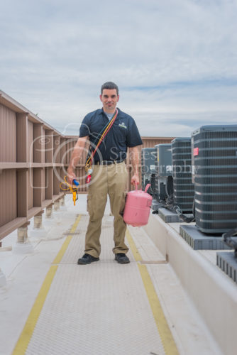 hvac technician with repair tools refrigerant, gauges, meter, standing next to condensing units on roof